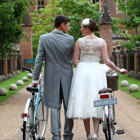 Bride and groom walking with bikes