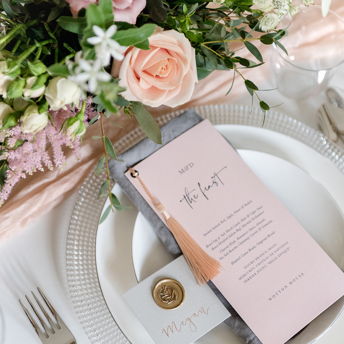 A place setting with blush coloured stationery